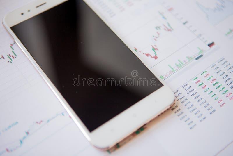 Смартфон с пустым экраном на предпосылке финансовых отчетов стоковое изображение