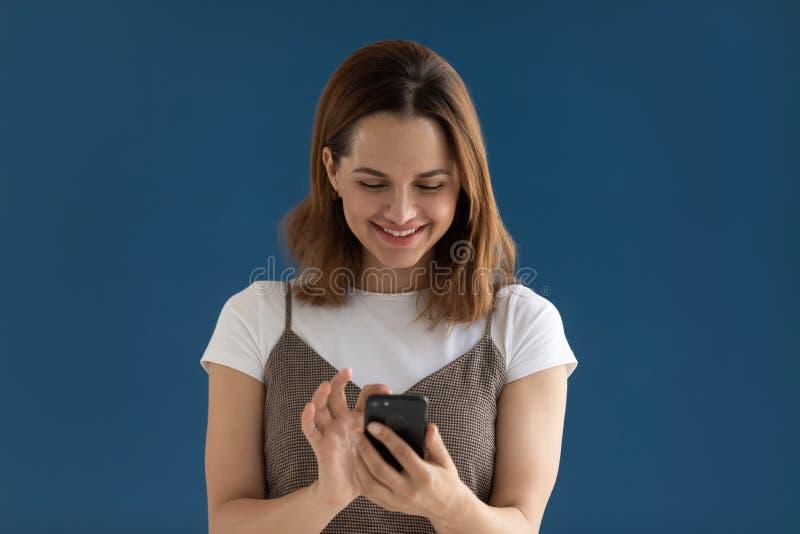 Смартфон удерживания молодой женщины усмехаясь используя новую съемку студии приложений стоковое изображение rf