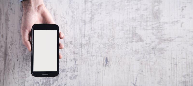Смартфон удерживания руки в современном белом столе стоковые фотографии rf