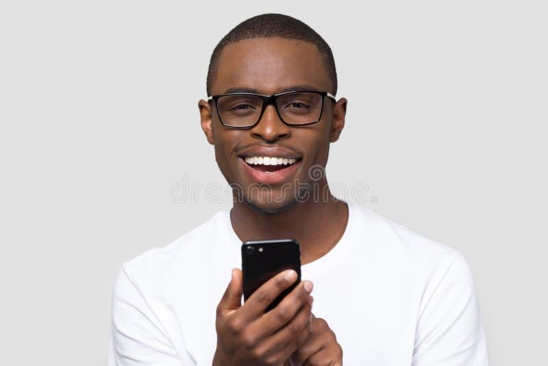 Смартфон удерживания человека портрета выстрела в голову усмехаясь африканский смотря камеру стоковое фото rf
