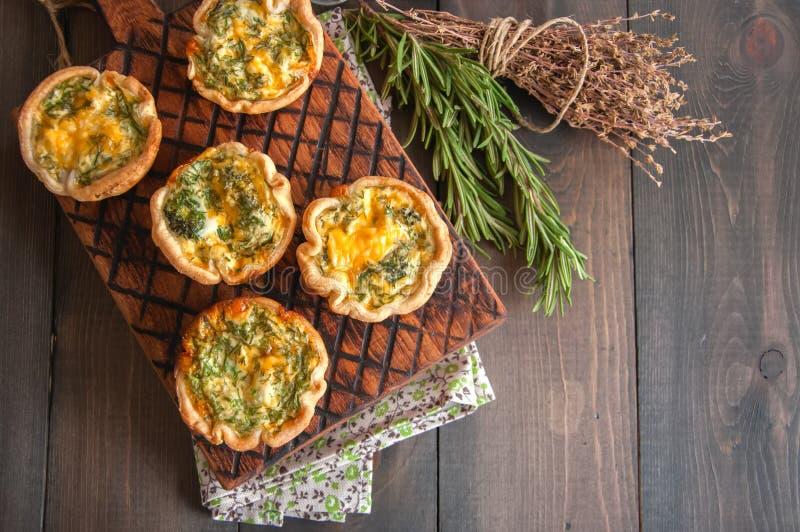 Смачные мини пироги кишей на деревянной доске Облупленные пироги теста стоковая фотография rf