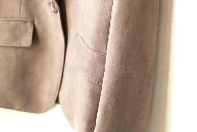 Смертная казнь через повешение куртки Брауна на вешалке одежд на белой предпосылке стоковые фотографии rf