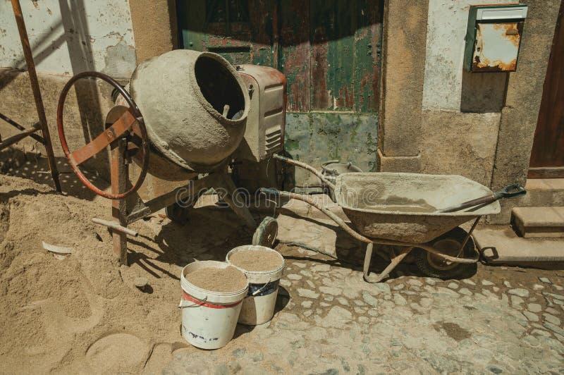 Смеситель цемента с ведрами pushcart и песка в строительной площадке стоковые изображения rf