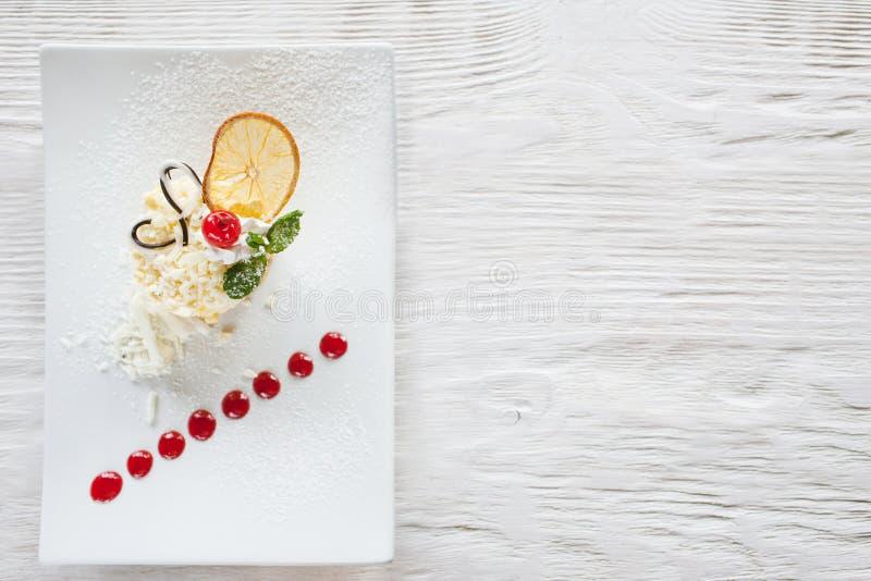 Сметанообразный оранжевый десерт на белом деревянном столе стоковая фотография rf