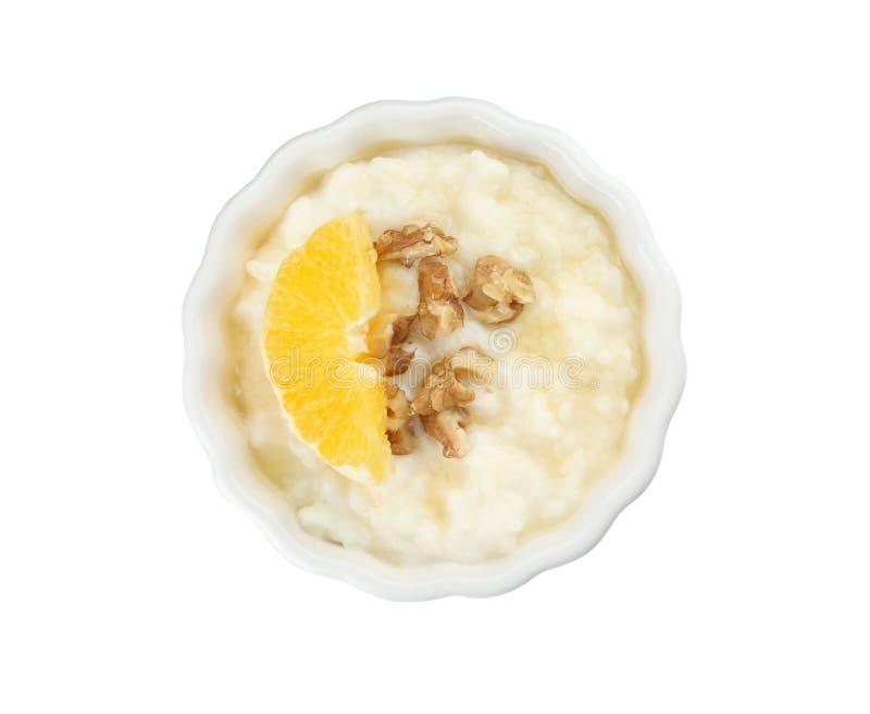 Сметанообразный рисовый пудинг с оранжевым куском и грецкие орехи в ramekin на белой предпосылке стоковые фото