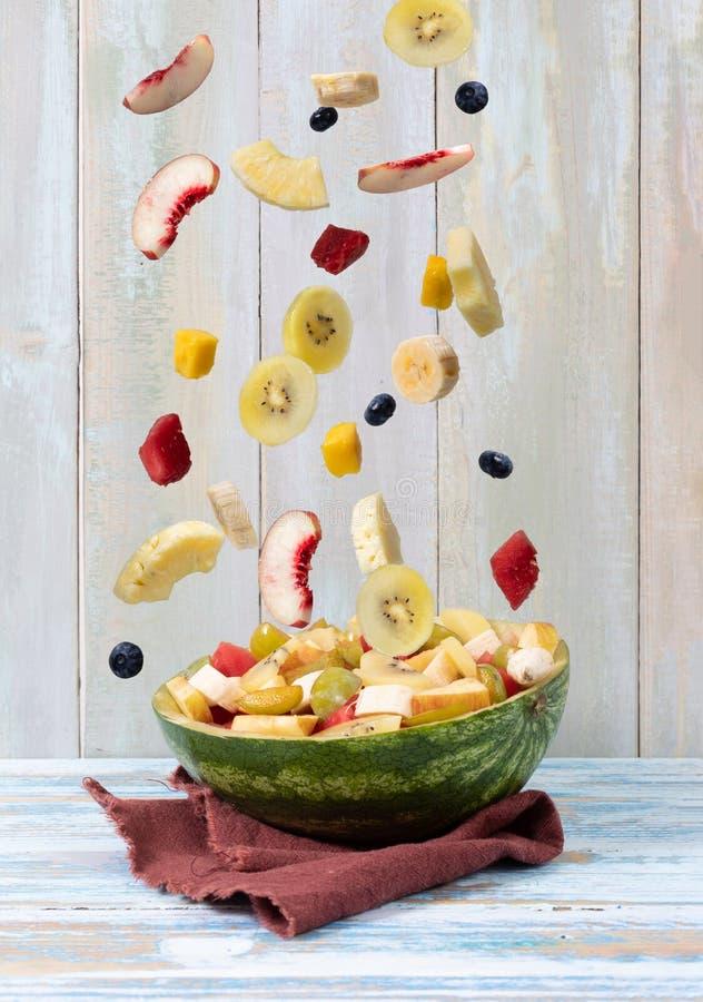 Смешанные падая плоды в пустом арбузе на деревянной предпосылке стоковые фото