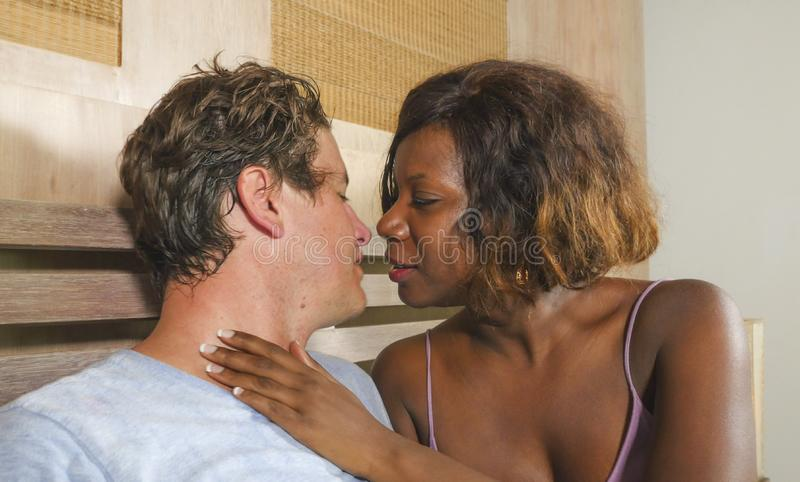 Смешанные пары этничности в любов прижимаясь совместно дома в кровати с девушкой или женой красивого шаловливого черного афро аме стоковые фото
