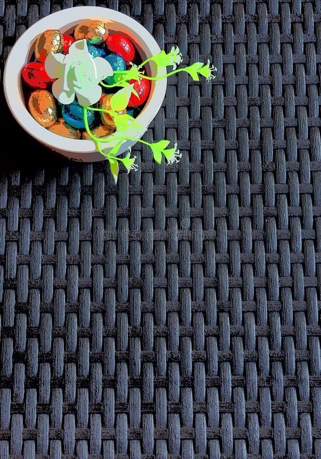 Смешанные покрашенные пасхальные яйца шоколада и темная плетеная предпосылка стоковое изображение