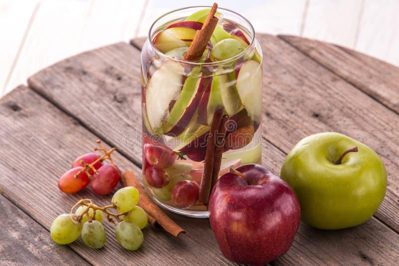 Смешивание воды свежих фруктов Flavored настоянное Яблока, виноградины и cinna стоковое изображение rf