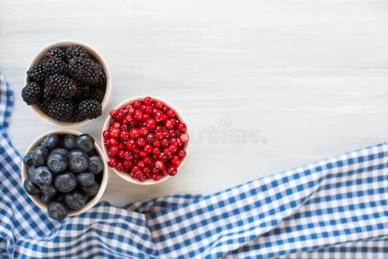 Смешивание зрелых ягод в шаре на белой деревянной предпосылке стоковые изображения rf