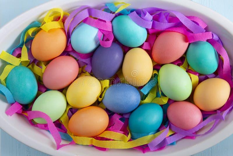Смешивание покрашенных ярких пасхальных яя в блюде с красочными бумажными лентами стоковые изображения rf