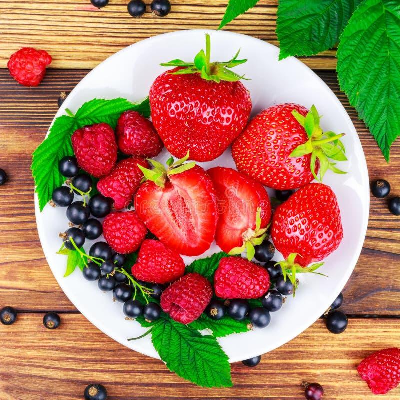 Смешивание свежих, зрелых ягод в плите на деревянной предпосылке стоковые фотографии rf