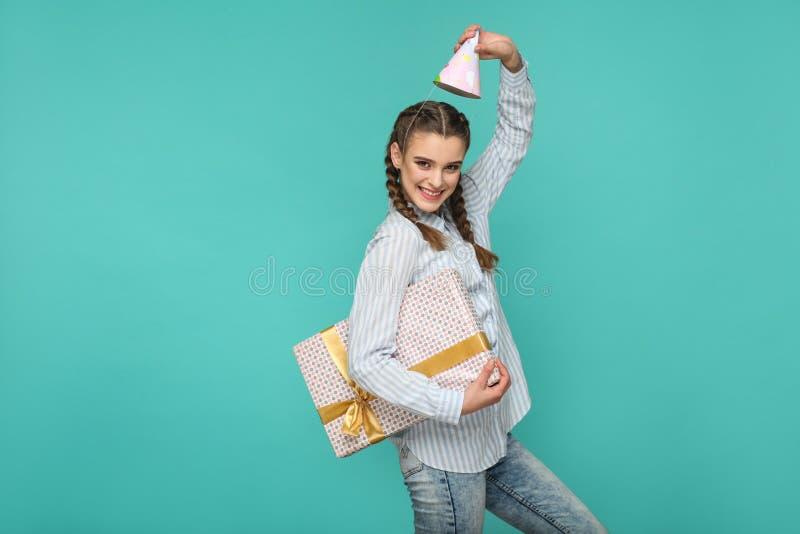 Смешная девушка в striped голубой рубашке стоя с поставленной точки подарочной коробкой a стоковая фотография rf