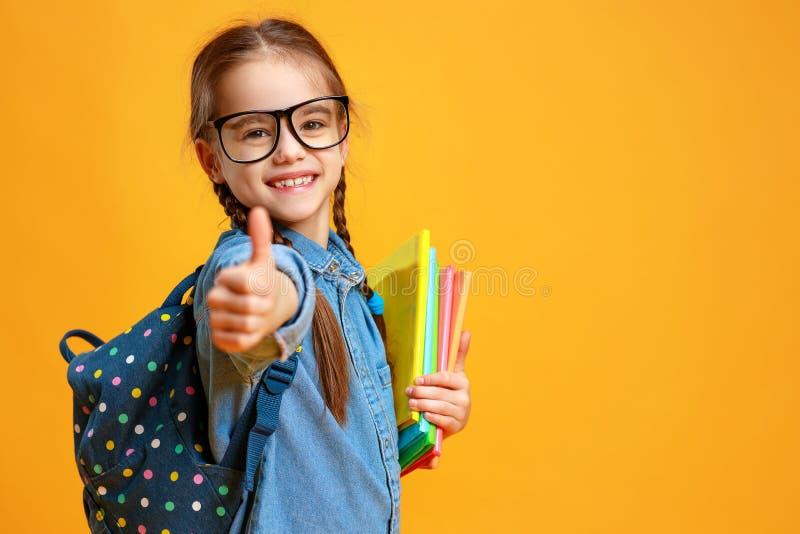 Смешная девушка девушки школы ребенка на желтой предпосылке стоковые изображения