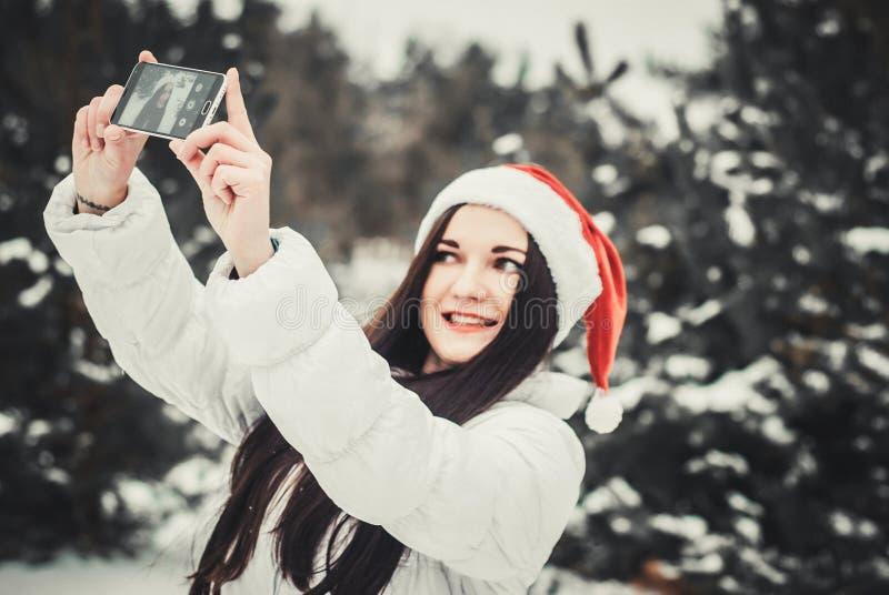 Смешная девушка принимая selfie Автопортрет девушки рождества внешний Женщина в одеждах зимы и шляпе Клауса на поле снега стоковые изображения rf