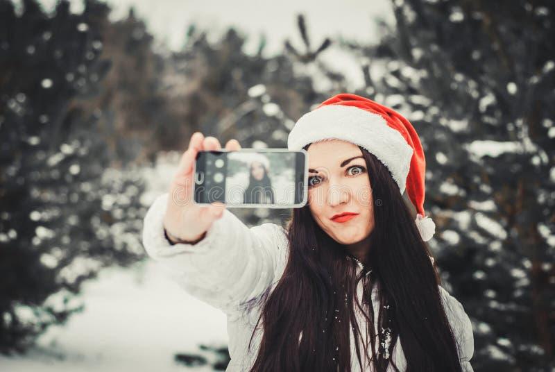 Смешная девушка принимая selfie Автопортрет девушки рождества внешний Женщина в одеждах зимы и шляпе Клауса на поле снега стоковое фото rf