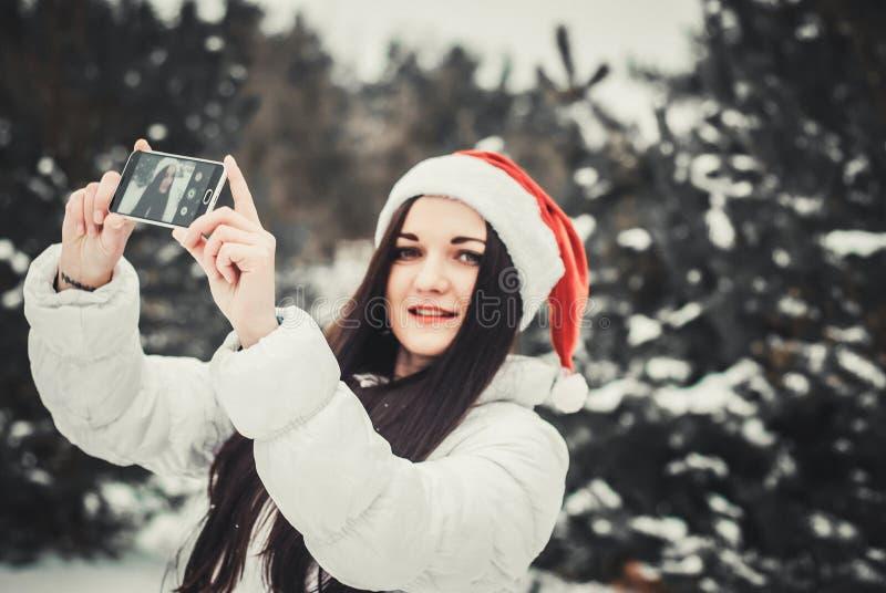 Смешная девушка принимая selfie Автопортрет девушки рождества внешний Женщина в одеждах зимы и шляпе Клауса на поле снега стоковые фото
