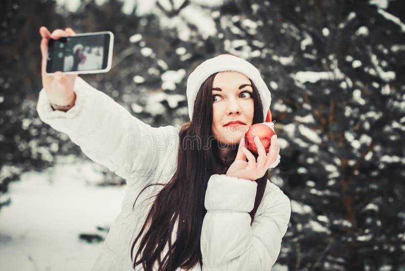 Смешная девушка принимая selfie Автопортрет девушки рождества внешний Женщина в одеждах зимы и шляпе Клауса на поле снега стоковое изображение