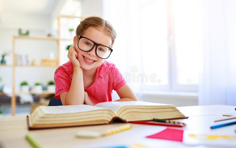 Смешная девушка ребенка делая сочинительство домашней работы и читая дома стоковое фото rf