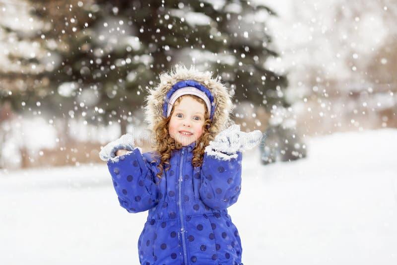 Смешная девушка подняла ее руки в воздухе, заразительном snowf стоковое фото
