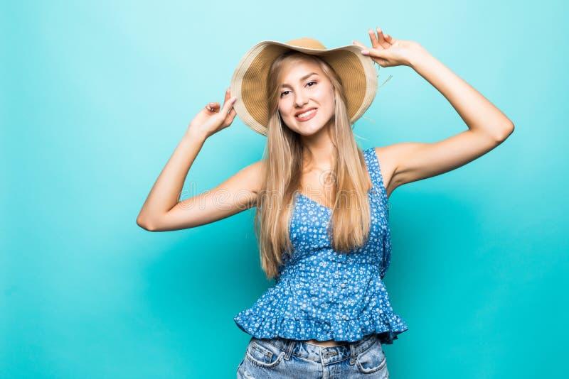 Смешная женщина в положении соломенной шляпы около голубой предпосылки стоковые изображения rf