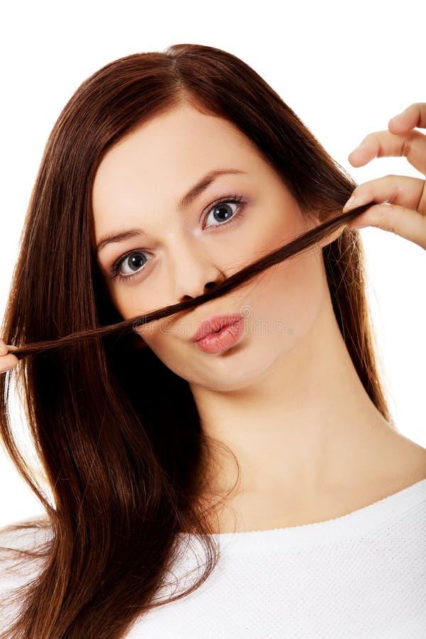 Смешная женщина студента кладя волосы любит усик стоковые фото