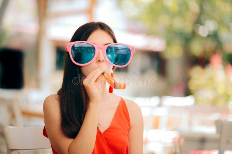 Смешная женщина с воздуходувкой рожка партии и слишком большими солнечными очками стоковое фото rf