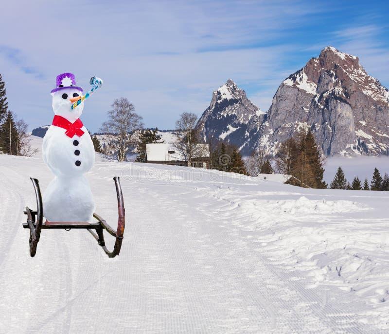 Смешная концепция рождества снеговика партии нося язык шляпы и ролика сползая вниз с наклона холма лыжи на сани стоковые фото