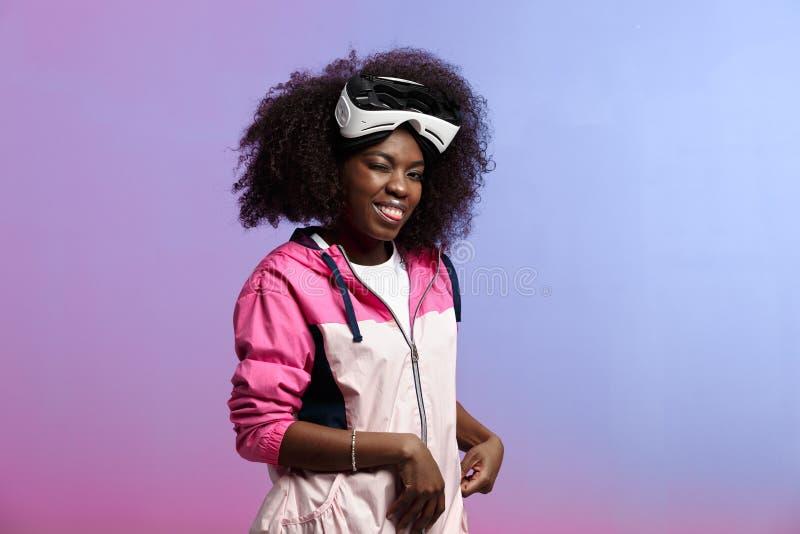 Смешная курчавая коричнев-с волосами девушка одетая в розовой куртке спорт носит на ее голове стекла виртуальной реальности в стоковое изображение