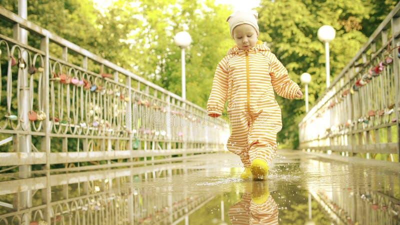 Смешная маленькая девочка в оранжевом водоустойчивом плаще и резиновых ботинках дождя идет на лужицу после дождя стоковые изображения rf