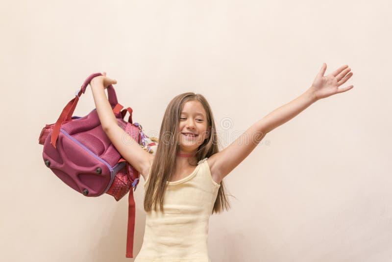 Смешная маленькая девочка при большой рюкзак скача и имея потеха против белой стены школа copyspace принципиальной схемы черных к стоковые изображения