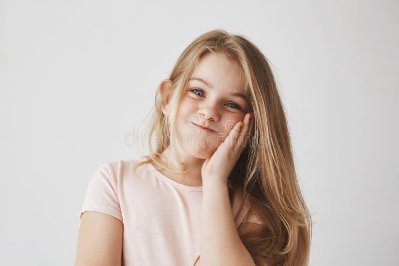 Смешная маленькая девочка при красивые длинные белокурые волосы смотря в камере, сжимающ щеку при рука, делая смешную сторону стоковое фото rf