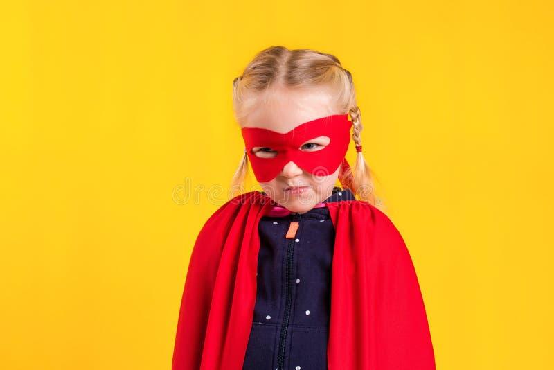 Смешная маленькая девушка ребенка супергероя силы в красном плаще и маске Концепция супергероя стоковое фото