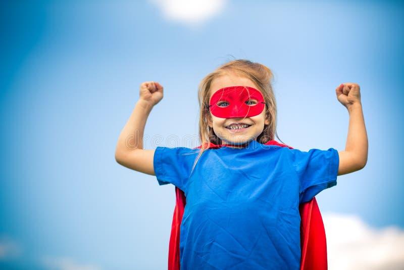 Смешная маленькая девочка играя супергероя силы стоковое фото rf