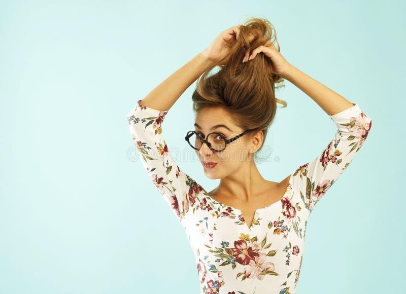 Смешная милая молодая женщина в круглых стеклах держа ее волосы вверх по ov стоковые фотографии rf