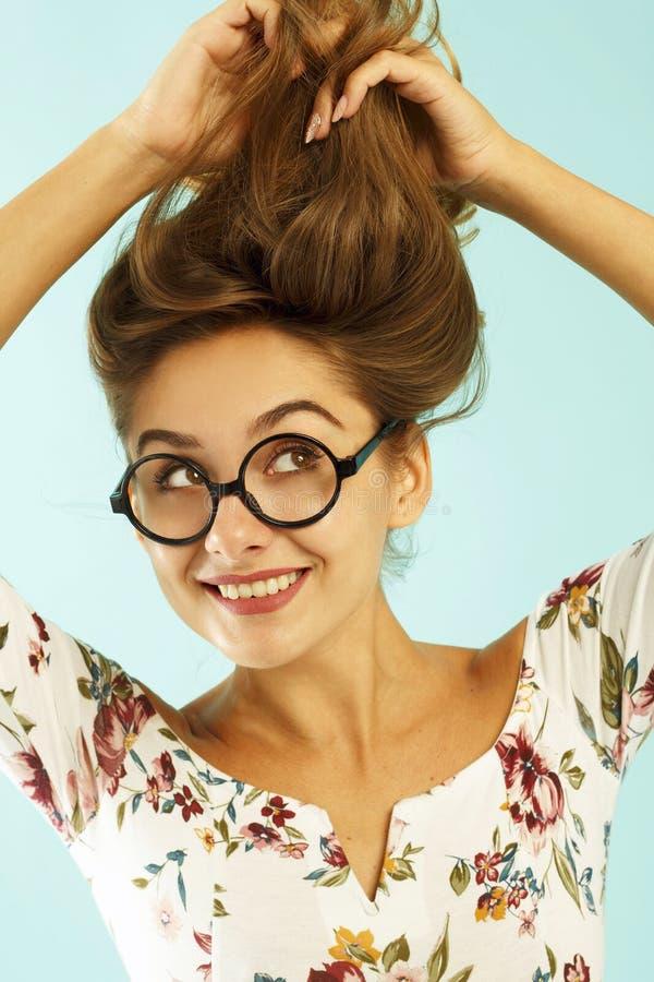 Смешная милая молодая женщина в круглых стеклах держа ее волосы вверх по ov стоковая фотография rf