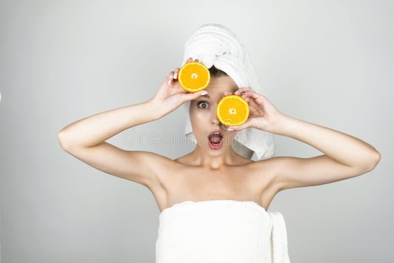 Смешная молодая женщина в белом полотенце на ее голове держа один апельсин около ее глаза и другой близко изолированной лбом бели стоковое фото rf