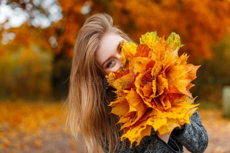 Смешная молодая счастливая молодая женщина в стильных одеждах держа роскошный букет золотой желтой листвы около стороны стоковая фотография