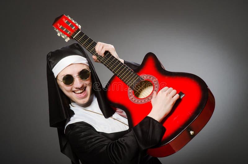 Смешная монашка с красный играть гитары стоковые изображения rf