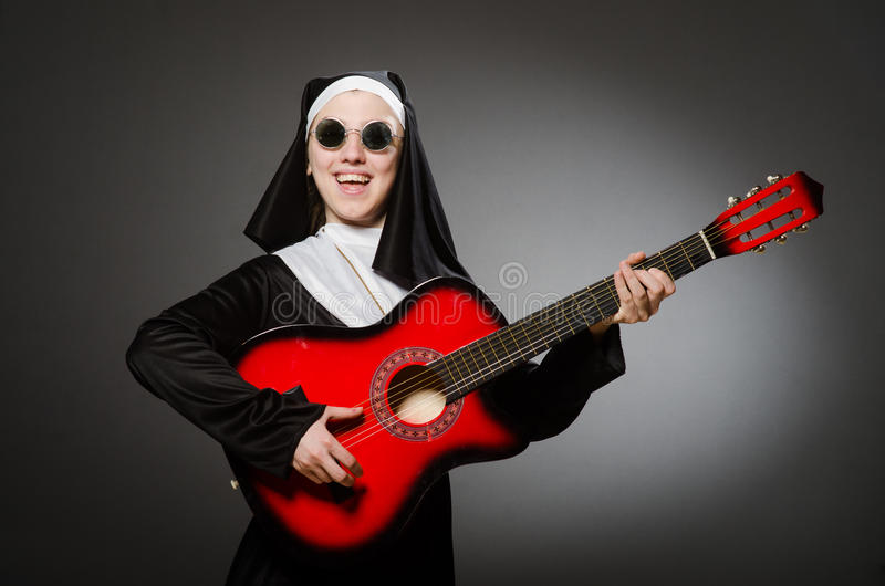Смешная монашка с красный играть гитары стоковые фото