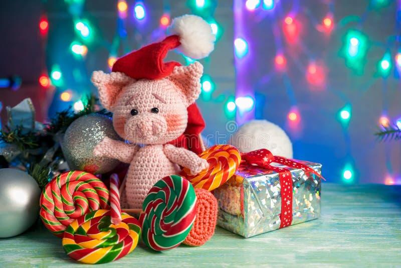 Смешная поздравительная открытка с Новым Годом 2019 Розовая свинья с леденцами на палочке на предпосылке с освещением стоковые изображения