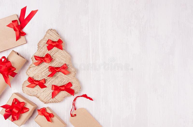 Смешная рождественская елка с красными смычками, подарочными коробками и ярлыками как decoretive граница на мягкой белой деревянн стоковое фото