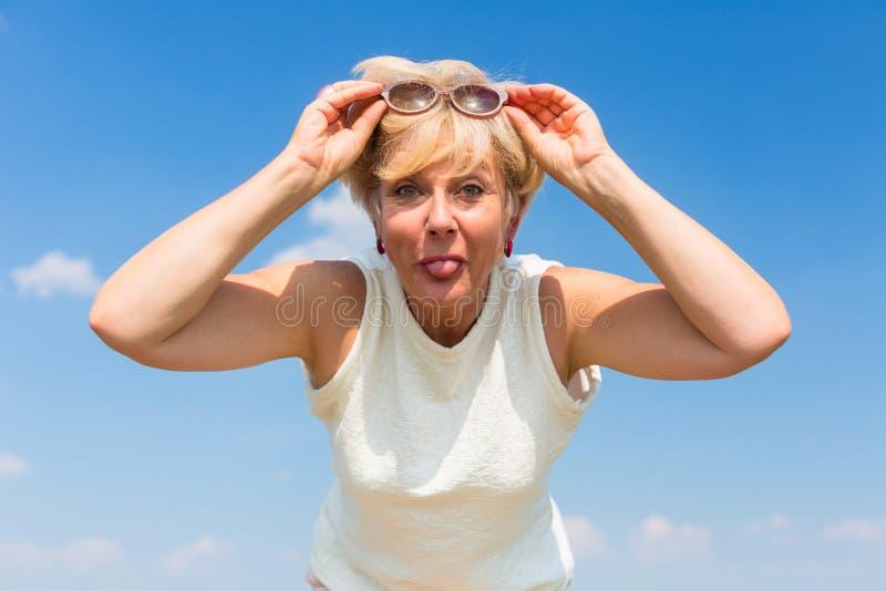 Смешная старшая женщина вставляя ее язык вне пока представляющ outdoors стоковое изображение rf