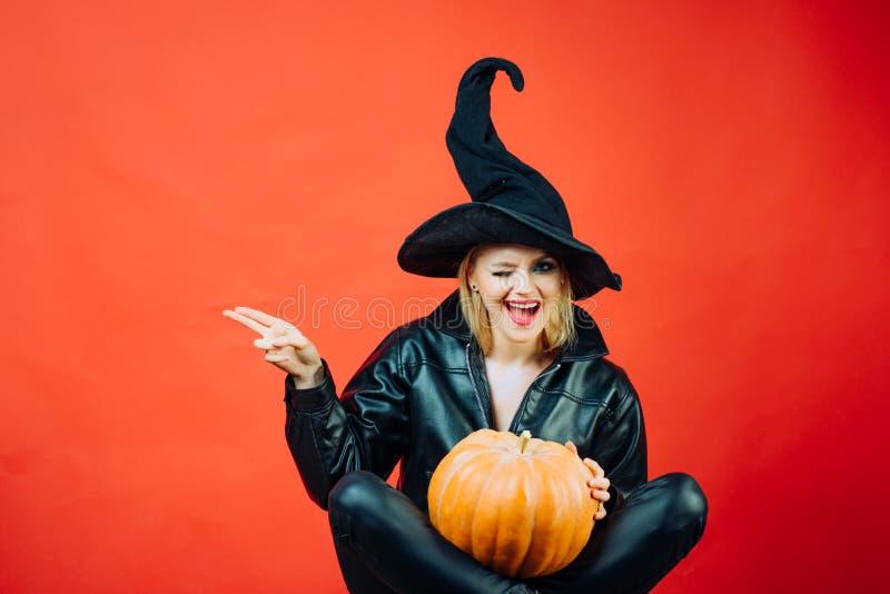 Смешная сторона и удивленная женщина motional молодые женщины в костюмах хеллоуина на партии над красной предпосылкой с тыквой стоковые изображения rf