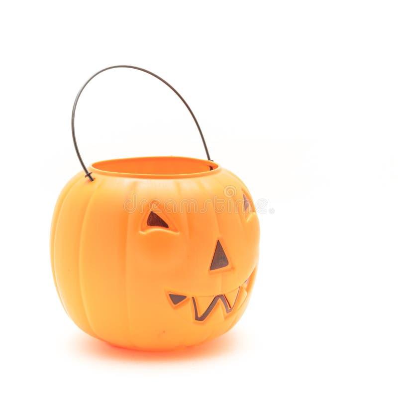 Смешная сторона на пластичном ведерке тыквы хеллоуина изолированном на белизне стоковое фото