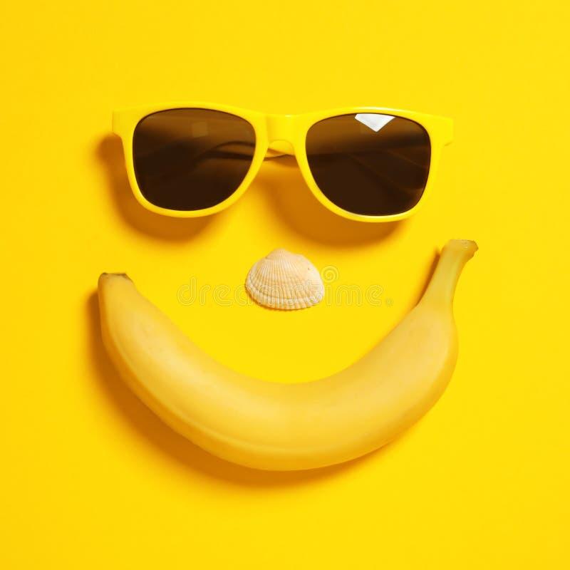 Смешная сторона солнечных очков, банана и seashell на предпосылке цвета Аксессуары пляжа стоковое фото rf