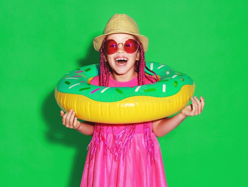 Смешная счастливая девушка ребенка в платье лета розовом с плавая донутом круга на зеленой предпосылке стоковое изображение rf