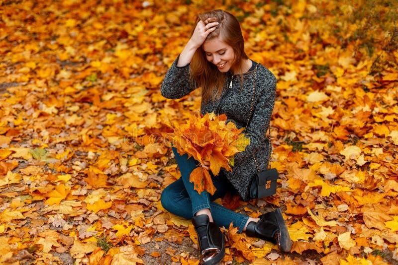 Смешная счастливая молодая женщина в модных теплых одеждах в ботинках отдыхает сидеть на том основании среди желтой листвы стоковая фотография rf