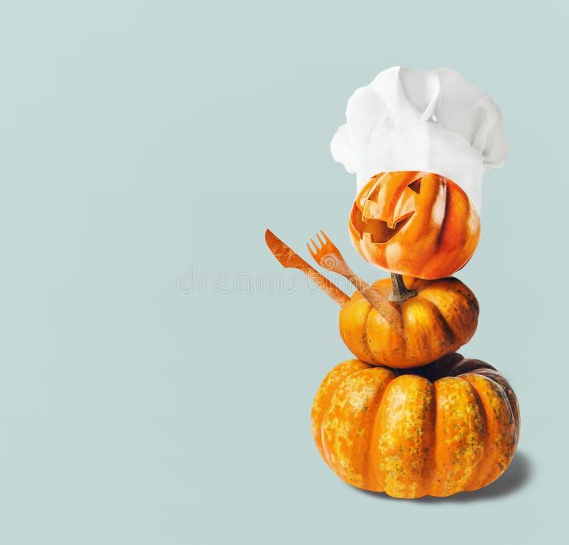 Смешная тыква Джек с шляпой шеф-повара и руки делают с столовым прибором, с космосом экземпляра Варить хеллоуина и благодарения стоковое фото rf