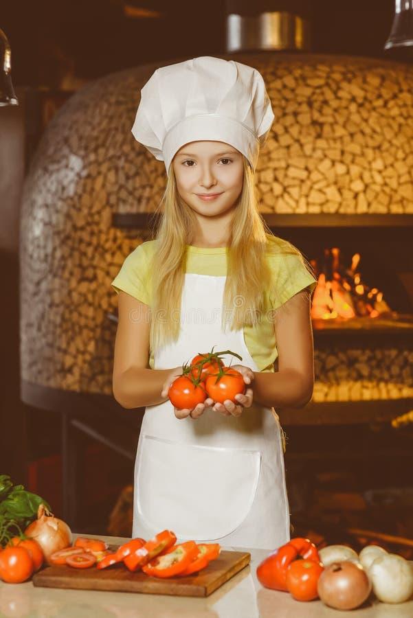 Смешная усмехаясь девушка шеф-повара держа томаты на стоковые фотографии rf